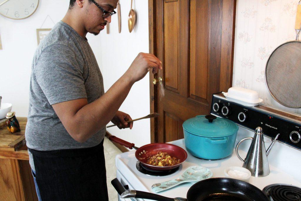 Hispanic chef seasoning huevos rancheros