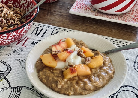 bowl of cooked oats topped with plain Greek yogurt, fresh peaches and toasted pecans, made with Nature's yoke eggs