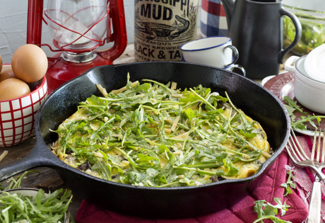 gluten-free frittata made with Nature's Yoke eggs, filled with bacon and mushrooms and topped with fresh arugula in cast iron skillet