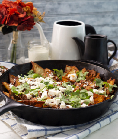 breakfast chilaquiles made with corn tortillas and Nature's Yoke eggs, topped with crumbled cheese in a cast iron skillet