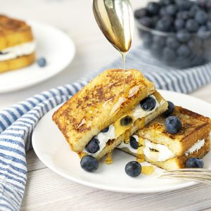 Blueberry cream cheese stuffed french toast on a white plate glazed with honey.